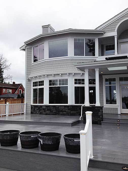 Empty black pots in the deck sit next to the white handrail.