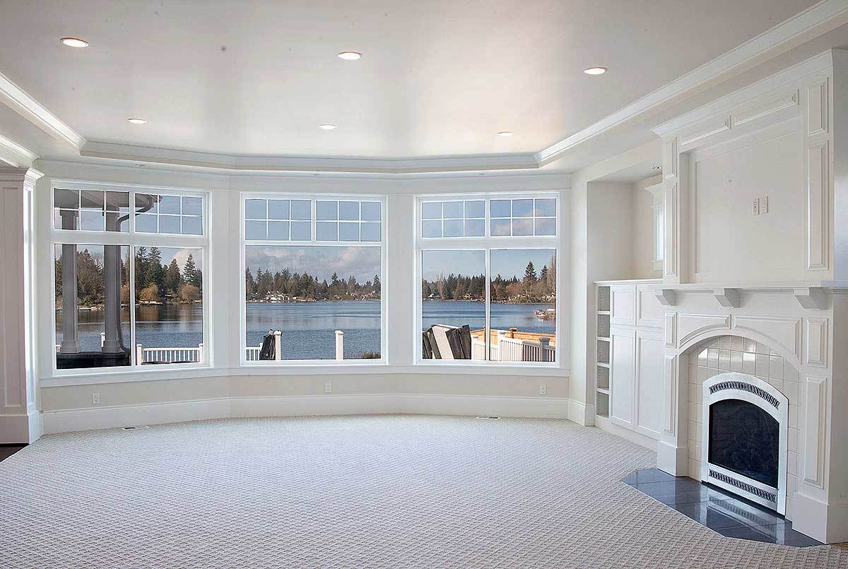 The great room has an arched fireplace and a tray ceiling fitted with recessed lights.