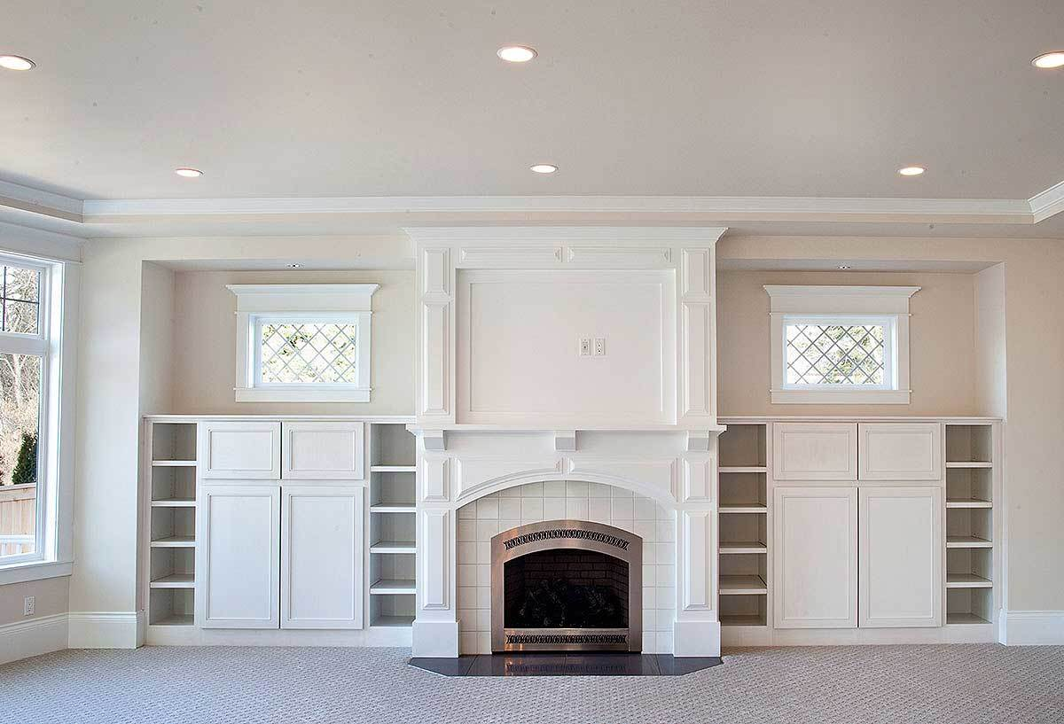 White built-in cabinets and shelves flank the fireplace.