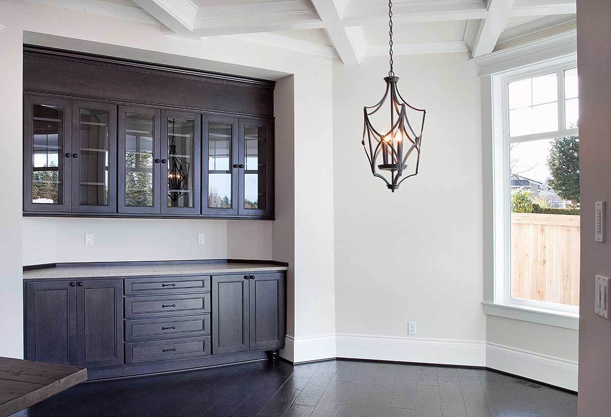 Hearth room with a bar and a wrought iron chandelier that hangs from the coffered ceiling.
