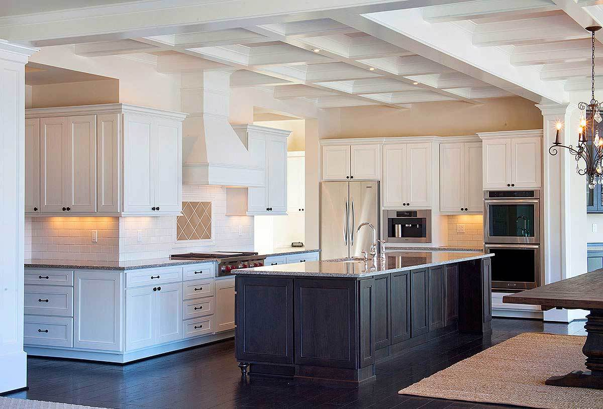 The coffered ceiling extends to the kitchen with white cabinetry, stainless steel appliances, and an immense island.
