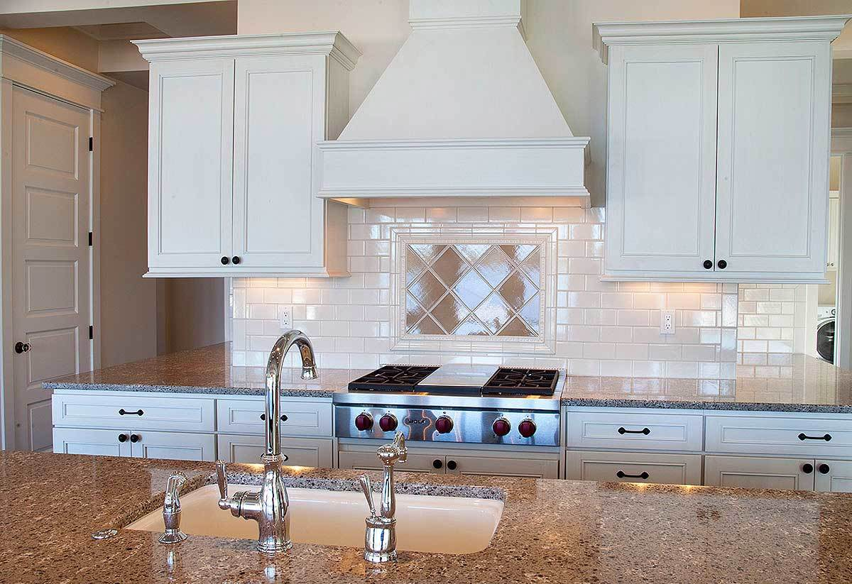 The granite top island is fitted with an undermount sink and chrome fixtures.