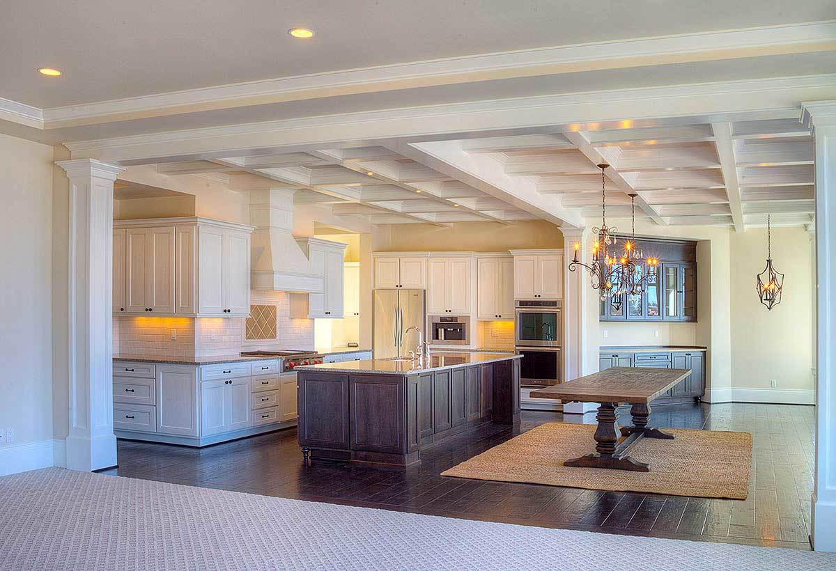 Across the kitchen is the dining area with candle chandeliers and a wooden table over a jute area rug.