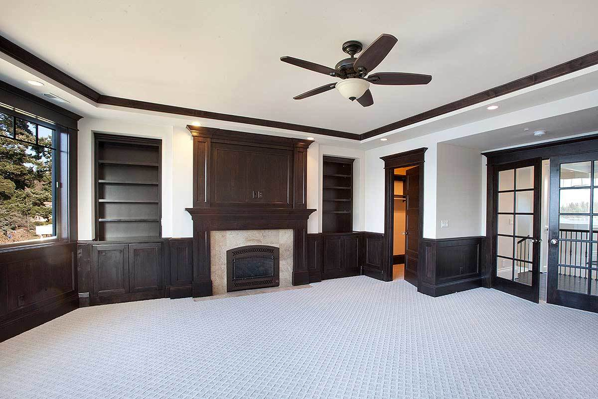 Home office with walk-in closet, marble fireplace, and dark wood built-ins.