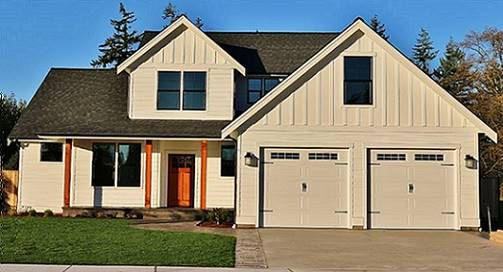Front exterior view showing the double garage, a large dormer window, and a covered porch lined with wooden columns.