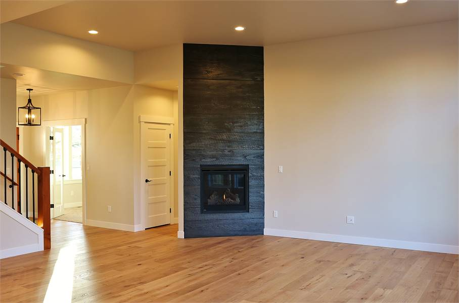 Living room with light hardwood floor, glass-enclosed fireplace, and beige walls.