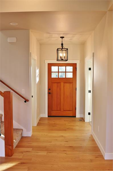 The foyer has a wooden entry door, caged pendant light, and a regular ceiling.