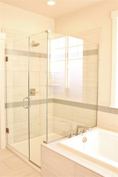 This bathroom is equipped with a drop-in bathtub and a walk-in shower enclosed in frameless glass panels.