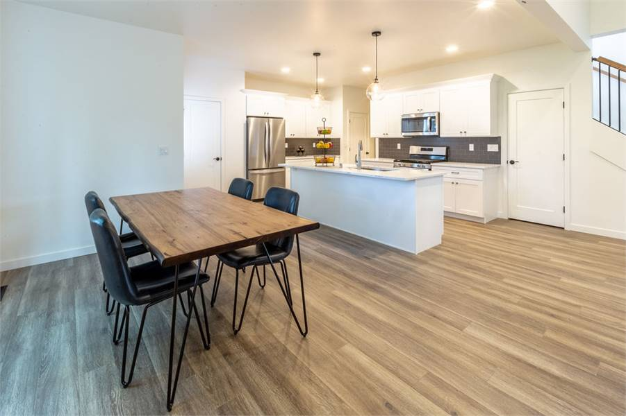 The dining area offers black leather chairs and a rectangular dining table that matches the hardwood flooring.