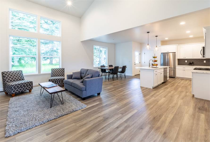 Family room with gray sectional, patterned chairs, and a wooden coffee table that sits on a shaggy area rug.