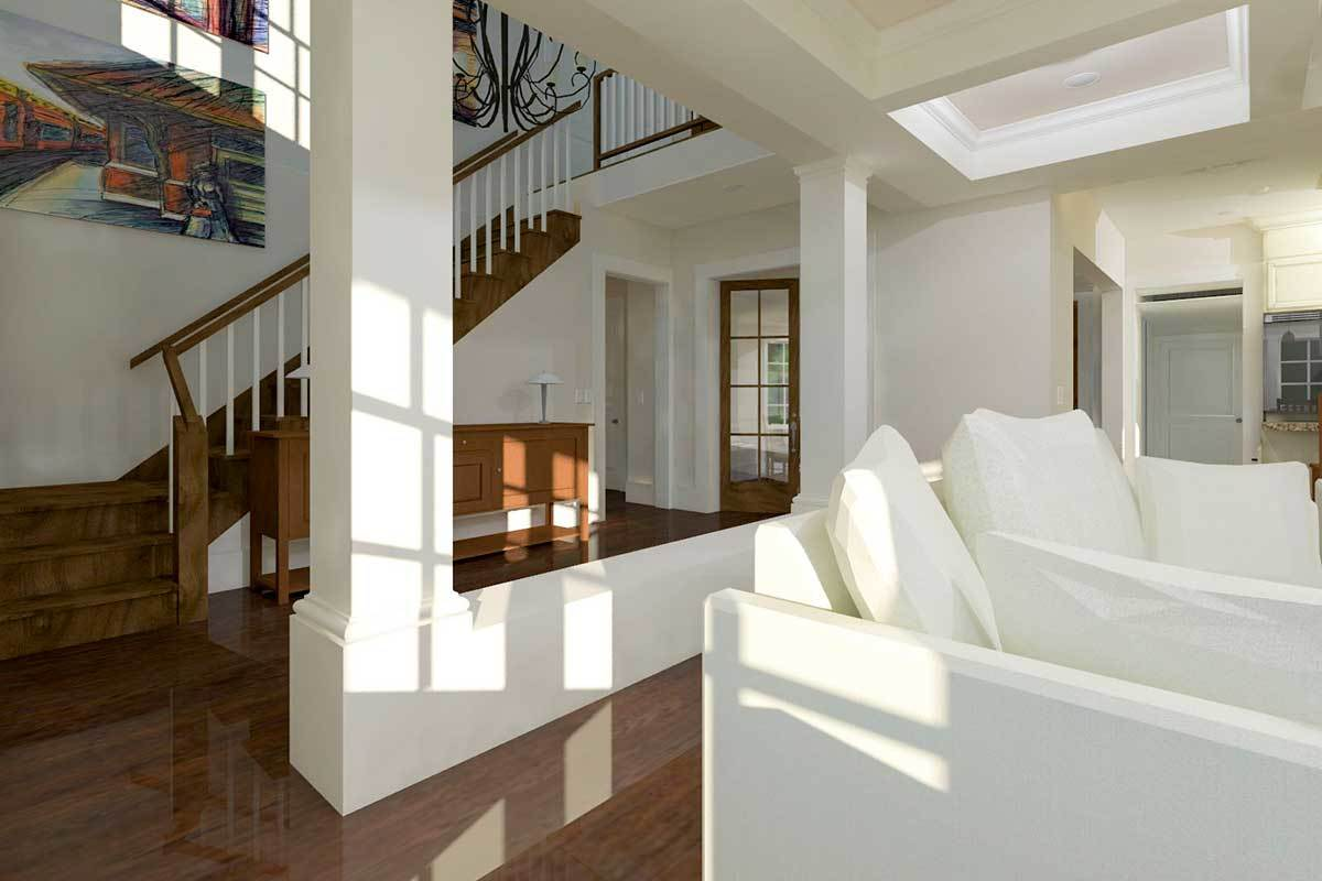 Foyer across the living room with a wooden console table and a traditional staircase.