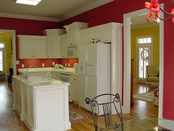 Eat-in kitchen with white appliances and cabinetry, double bowl sink, and an island bar.