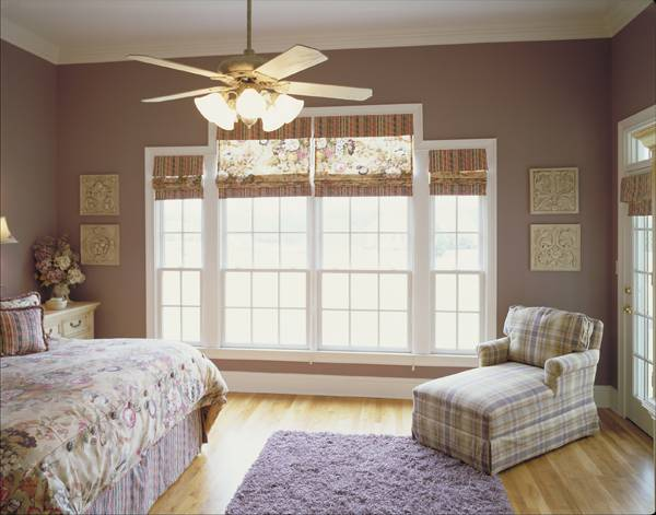 The primary bedroom has a skirted bed, a checkered chaise lounge, a shaggy rug, and white framed windows dressed in striped and floral shades.