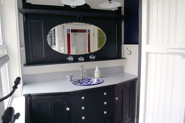 This bathroom features a black vanity with decorative porcelain sink, quartz countertop, and an oval mirror.