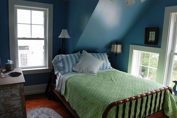 Bedroom with vaulted ceiling, blue walls, a cozy bed, and a distressed dresser.