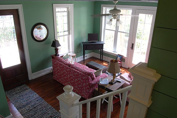 View of the living room from the staircase showing a red patterned sofa, dark wood tables, and a small TV.