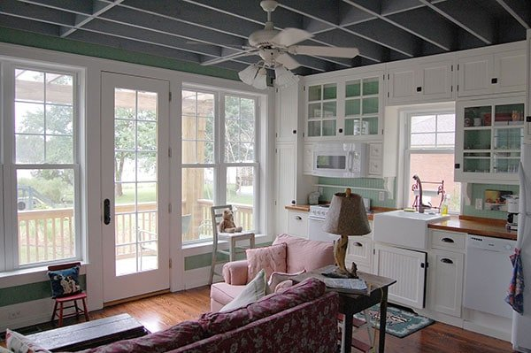 Adjacent to the living room is the kitchen with white cabinets, sage green walls, and a farmhouse sink.