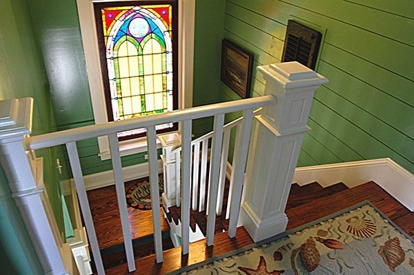 Staircase landing adorned with a glass stained window and artworks that are mounted against the green shiplap wall.