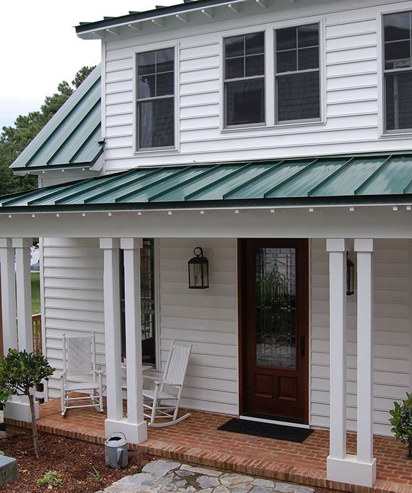 Home entry with a wooden front door, white rocking chairs, and double columns framing the porch.