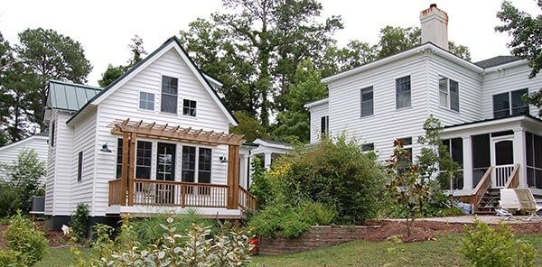 View of the house from the backyard showing the white horizontal siding, green gables, and rear pergola porch.