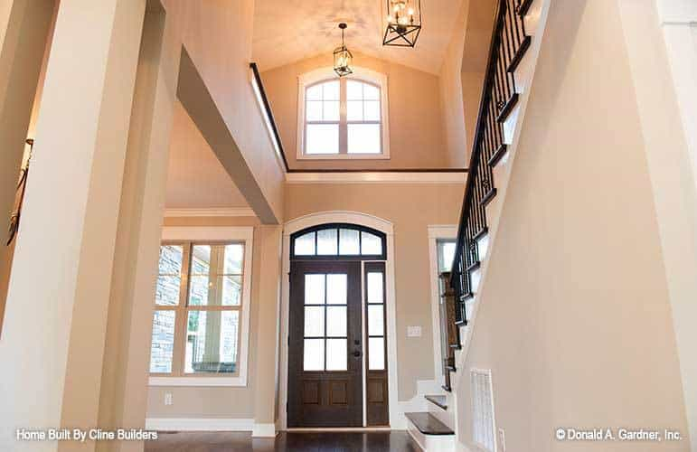 The foyer has a high vaulted ceiling, dark wood entry door, and lantern pendants.