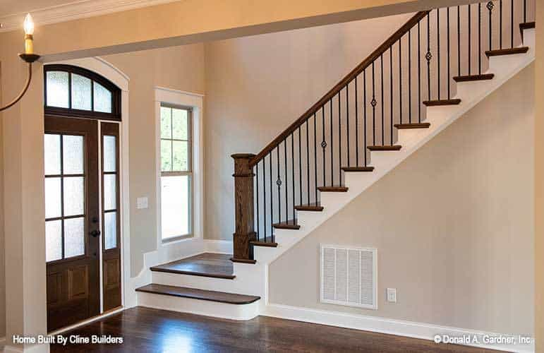 Staircase with wooden treads and handrails matching with the front door.
