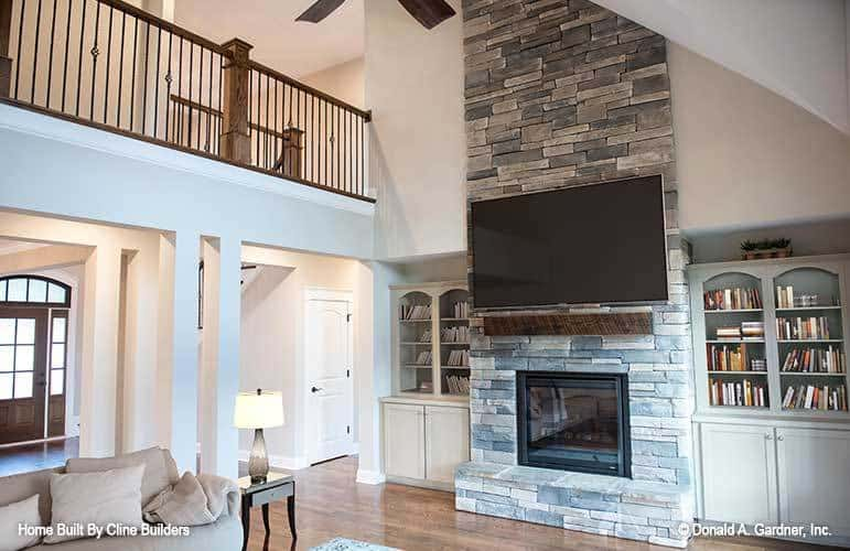 Stone brick fireplace in the living room flanked by white built-ins.