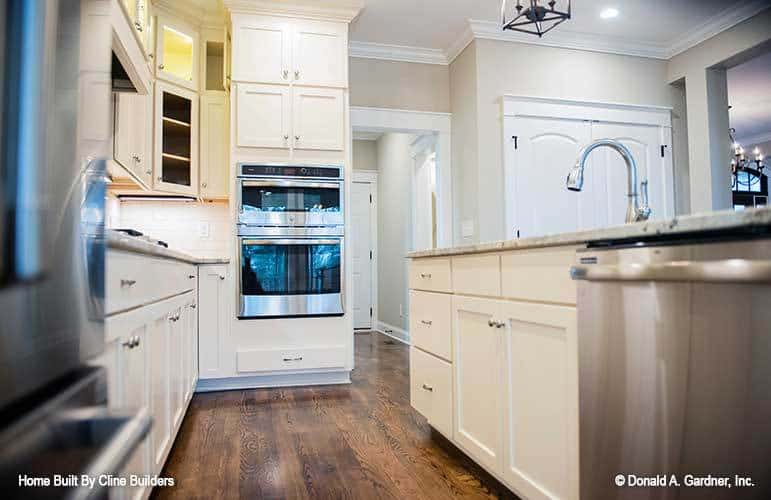 Double-wall oven and a walk-in pantry with a white double door complete the kitchen.