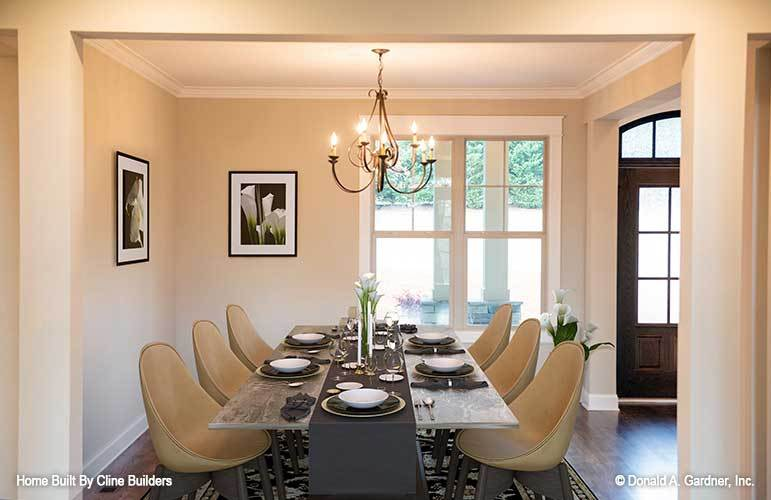 Formal dining room with a candle chandelier, round back chairs, rustic dining table, and black-framed artworks adorning the beige walls.