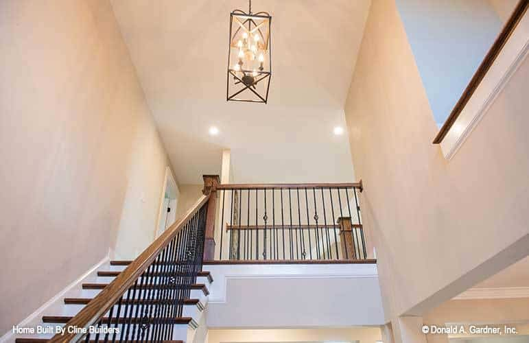 A large pendant light hanging from the high regular ceiling illuminates the staircase.