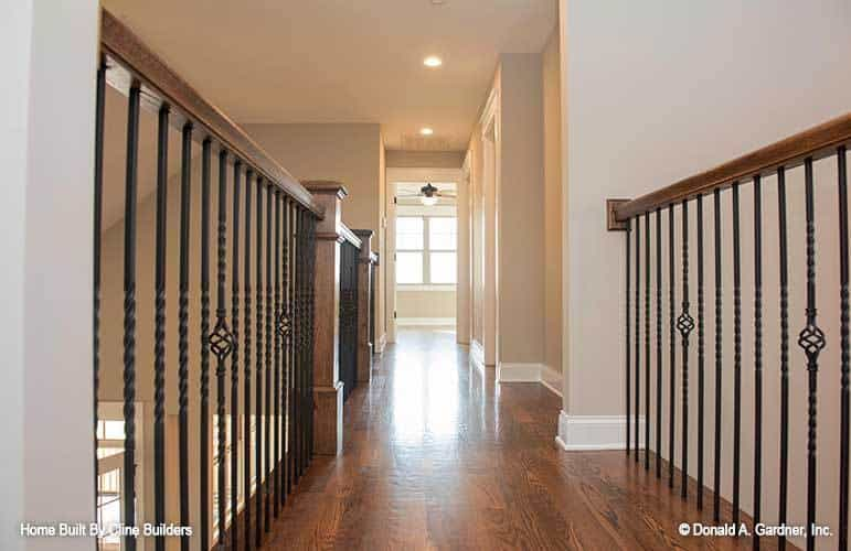 Balcony loft with hardwood floor and ornate wrought iron railings.