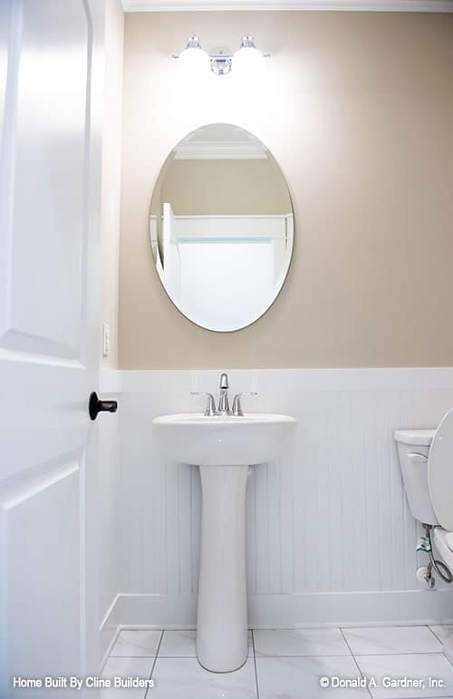 Powder room with a porcelain pedestal sink and an oval frameless mirror.