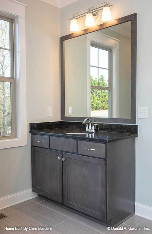 Another bathroom with dark wood vanity and a large framed mirror well-lit by glass sconces.