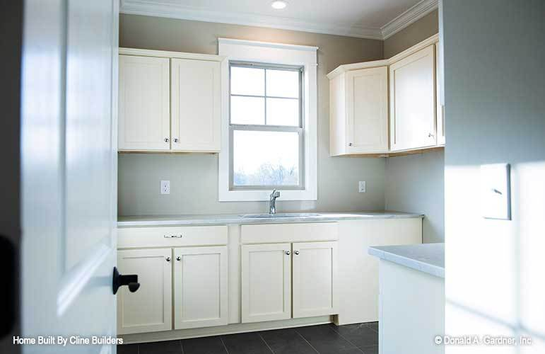 The utility room is filled with cream cabinets, undermount sink, and a white framed window.