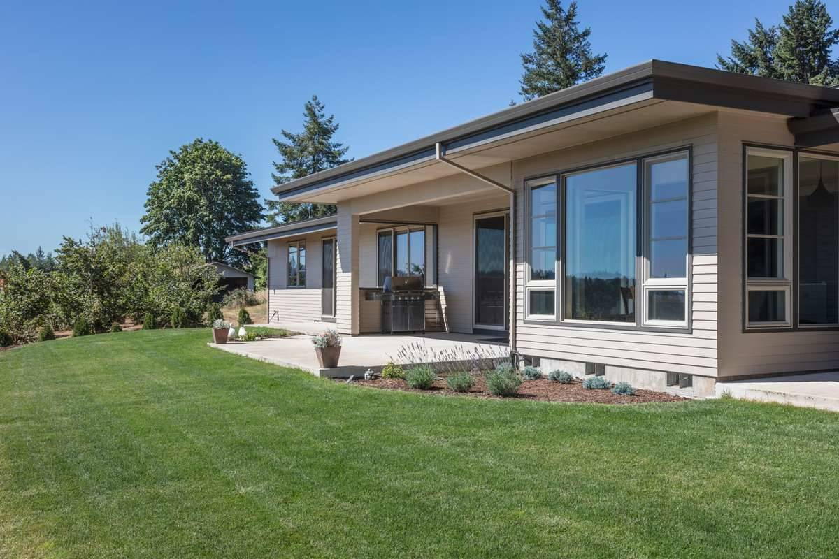 The lush green lawn surrounds the rear patio with a summer kitchen.