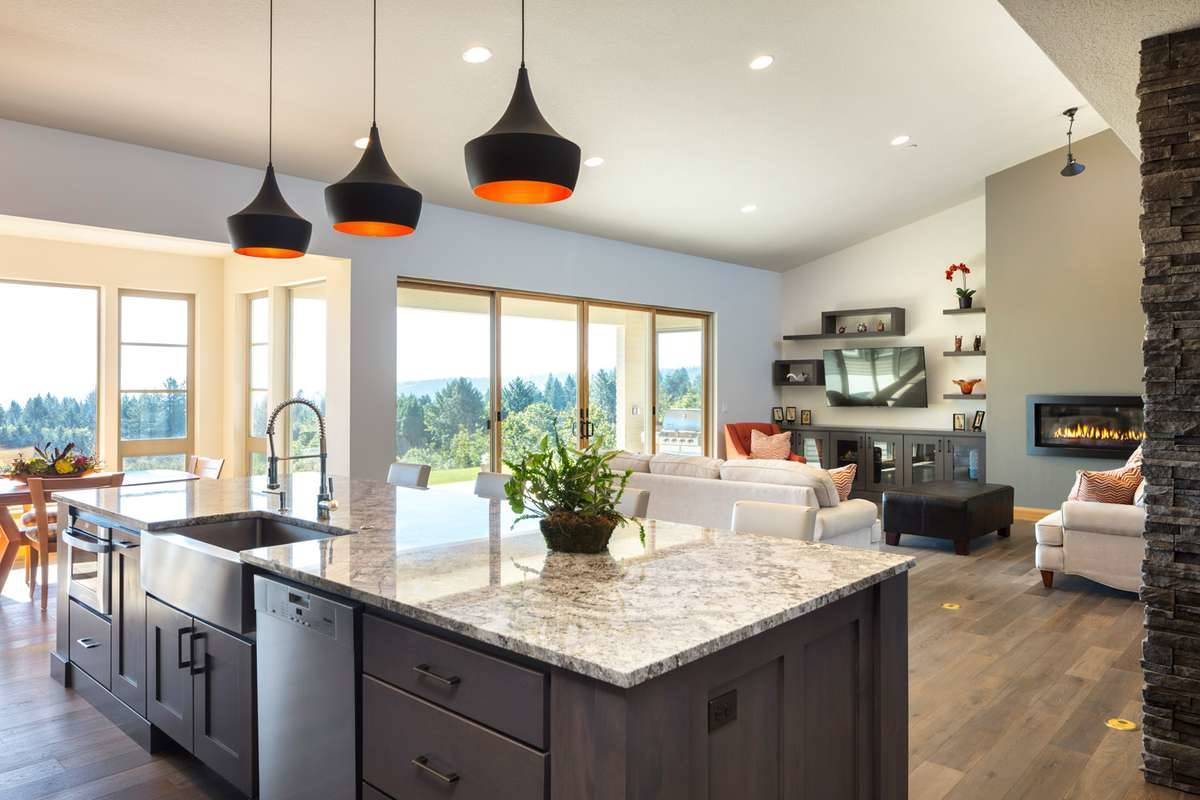 Black dome pendants illuminate the kitchen island that's fitted with a farmhouse sink and dishwasher.