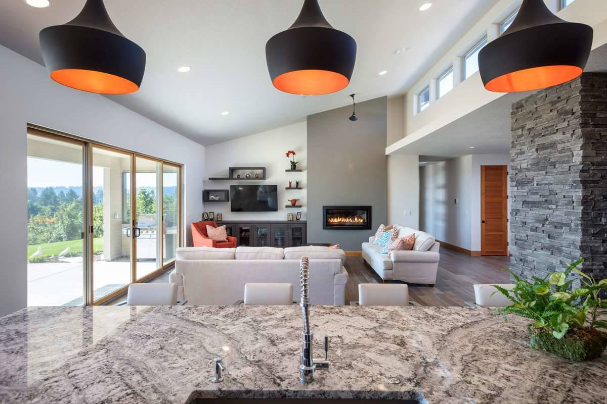 View of the living room from the kitchen island showing its vaulted ceiling and modern fireplace.