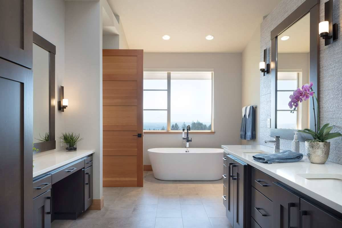 The primary bathroom has two vanities and a freestanding tub placed under the picture window.