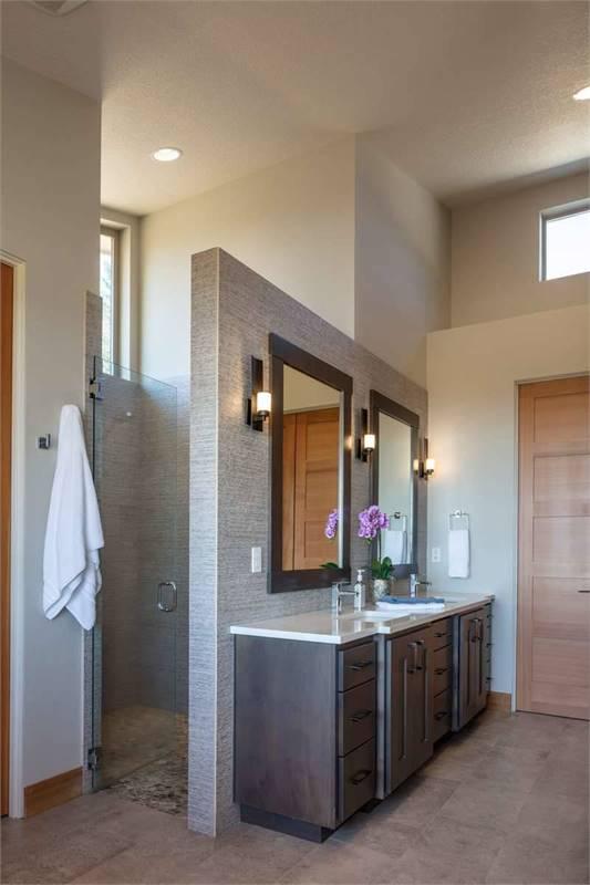 Behind the dual sink vanity is a walk-in shower enclosed in a glass hinged door.