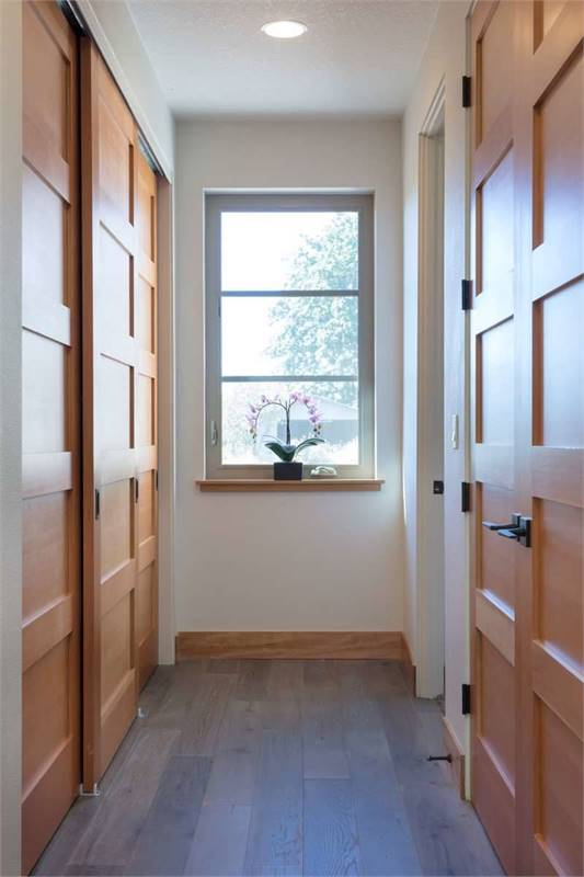 A hallway leading to the bedrooms with a framed window adorned by a potted plant.