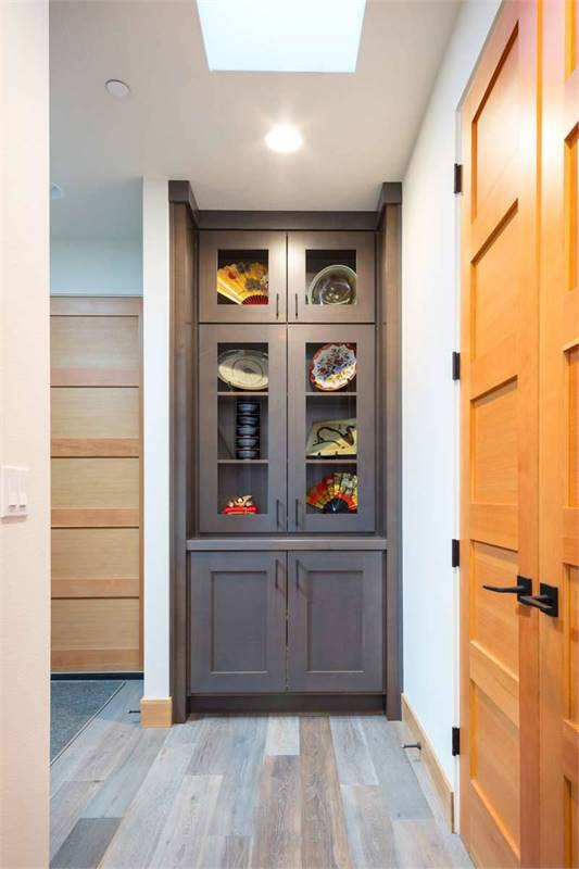 This hallway has a skylight and a built-in cabinet displaying ceramic plates and decorative fans.