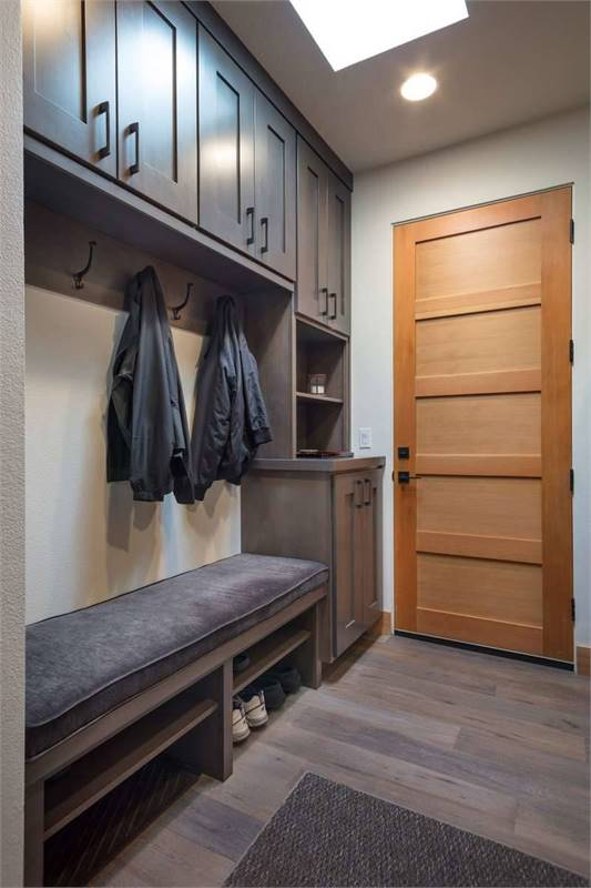 The mudroom is filled with wooden cabinets and a storage bench that doubles as a shoe rack.