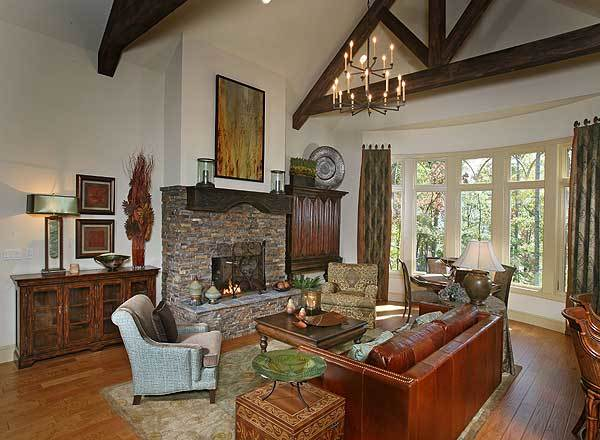 Living room with leather sofa, fabric armchairs, a stone fireplace, and a bow window dressed in patterned drapes.