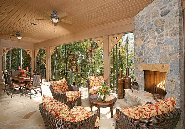 Covered lanai filled with a rectangular dining set, cushioned wicker chairs, and a large stone fireplace fixed in the corner wall.