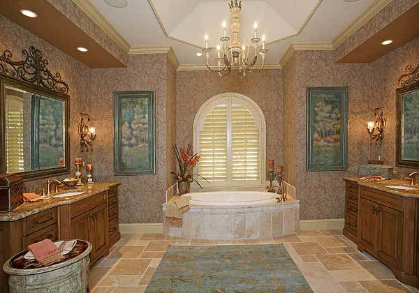 Primary bathroom with two wooden vanities, tray ceiling with a hanging chandelier, and a drop-in bathtub under the arched window.