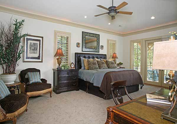 The primary bedroom has a leather tufted bed, dark wood nightstands, louvered windows, cushioned armchairs, and a wooden desk.