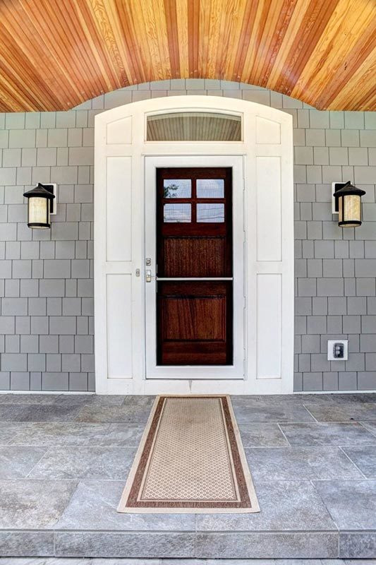 Home entry with outdoor sconces and a dark wood front door surrounded with white panels and a transom window.