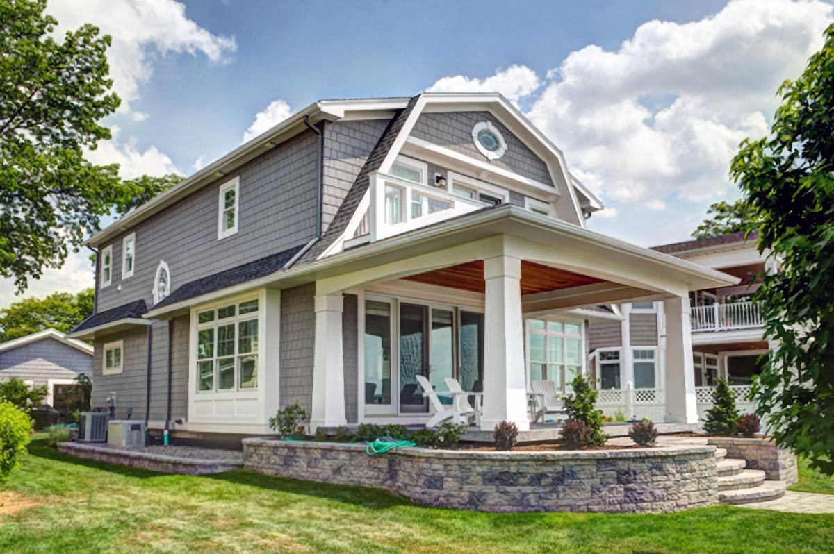Angled rear view with cedar shingle siding, varied rooflines, and white framed windows.