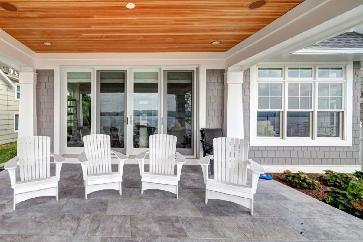 The covered porch has a wood-paneled ceiling and white lounge chairs over concrete flooring.