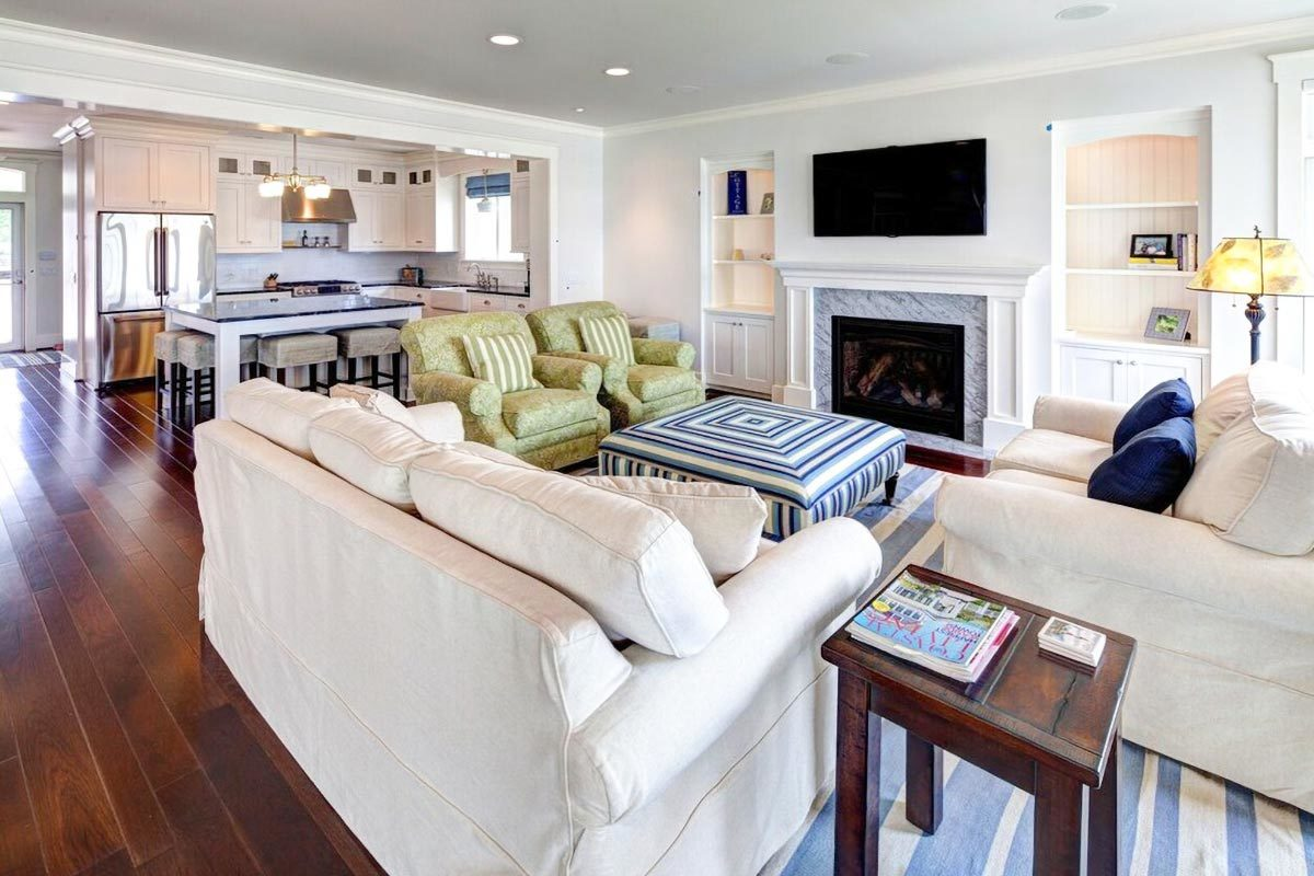 The living room has beige sectionals, green floral armchairs, a patterned ottoman, and a marble fireplace with a TV on top.